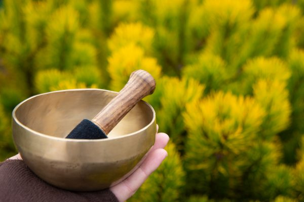Female hand in a glove without fingers holds a singing bowl with a stick on a blurred background of bright yellow-green pine.As an aid in meditation, yoga or a spiritual practice.