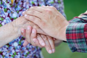 Young male hand holding an elderly woman's hand